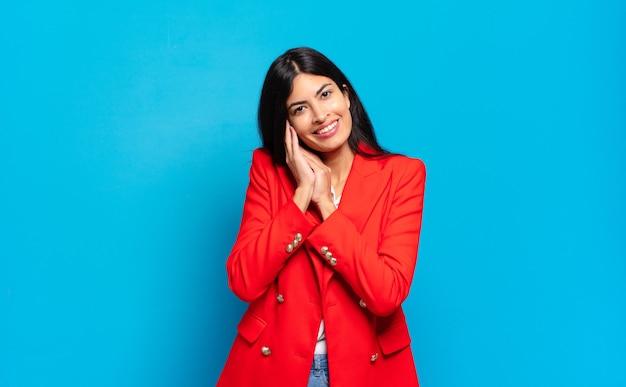 Młoda hiszpańska bizneswoman zakochana i wyglądająca uroczo, uroczo i szczęśliwie, uśmiechając się romantycznie z rękami przy twarzy