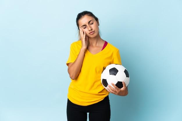 Młoda hiszpańska grający na pozycji napastnika kobieta na białym tle na niebieskiej ścianie z bólem głowy