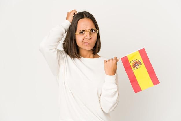 Młoda hiszpańska kobieta rasy mieszanej trzymająca hiszpańską flagę będąc w szoku, przypomniała sobie ważne spotkanie.