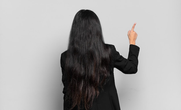 Młoda hiszpańska kobieta stojąca i wskazująca na sprzeciw na przestrzeni kopii
