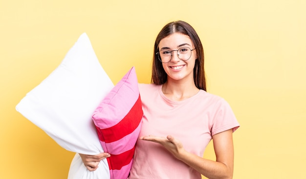 Młoda hiszpańska kobieta uśmiecha się radośnie, czuje się szczęśliwa i pokazuje koncepcję. koncepcja piżamy i poduszki