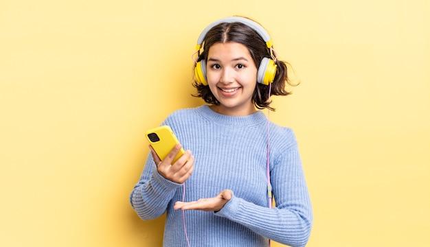 Młoda hiszpańska kobieta uśmiecha się radośnie, czuje się szczęśliwa i pokazuje koncepcję. koncepcja słuchawek i smartfona