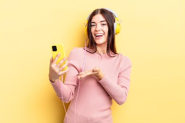 Młoda hiszpańska kobieta uśmiecha się radośnie, czuje się szczęśliwa i pokazuje koncepcję. koncepcja słuchawek i telefonu