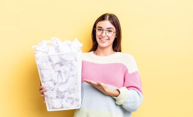 Młoda hiszpańska kobieta uśmiecha się radośnie, czuje się szczęśliwa i pokazuje koncepcję. koncepcja śmieci awaria
