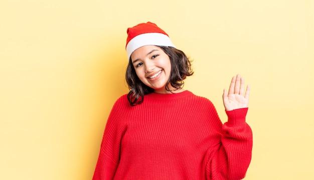 Młoda hiszpańska kobieta uśmiecha się radośnie, macha ręką, wita i wita. koncepcja bożego narodzenia