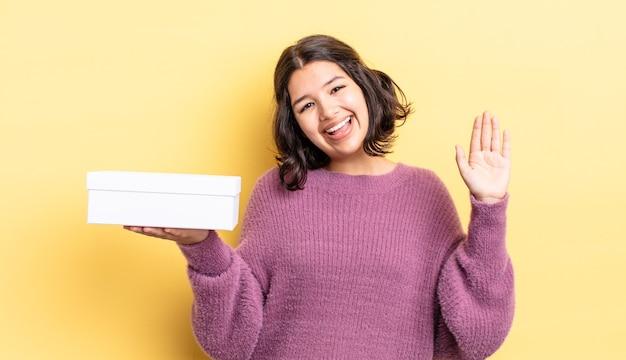 Młoda hiszpańska kobieta uśmiecha się radośnie, macha ręką, wita i wita. koncepcja pustego pudełka