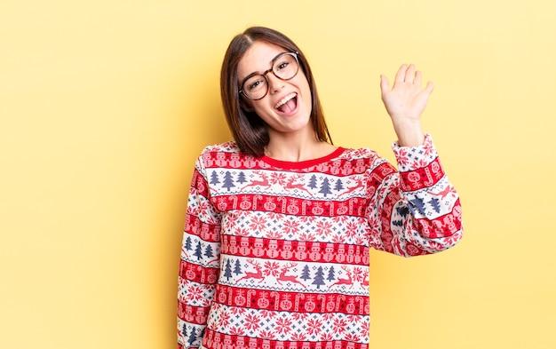 Młoda hiszpańska kobieta uśmiecha się radośnie, macha ręką, wita i wita. koncepcja świąteczna i noworoczna