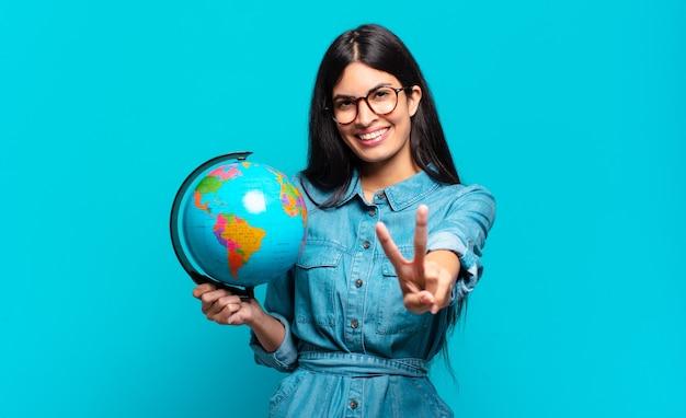 Młoda hiszpańska kobieta uśmiechnięta i patrząca przyjaźnie, pokazująca numer dwa lub drugi z ręką do przodu, odliczając w dół. koncepcja planety ziemi