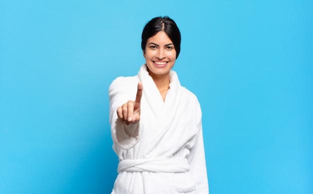 Młoda hiszpańska kobieta uśmiechnięta i patrząca przyjaźnie, pokazująca numer jeden lub pierwszy z ręką do przodu, odliczając w dół. koncepcja szlafrok