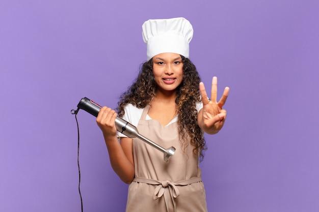 Młoda hiszpańska kobieta uśmiechnięta i patrząca przyjaźnie, pokazująca numer trzy lub trzeci z ręką do przodu, odliczając. koncepcja szefa kuchni