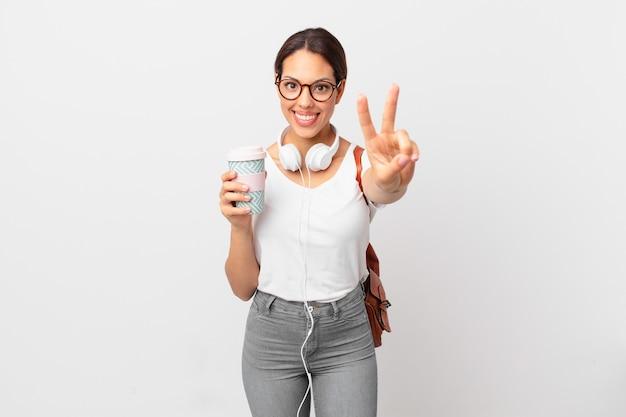 Młoda hiszpańska kobieta uśmiechnięta i szczęśliwa, gestykulująca zwycięstwo lub pokój. koncepcja studenta