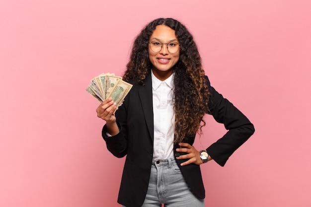 Młoda hiszpańska kobieta uśmiechnięta radośnie z ręką na biodrze i pewna siebie, pozytywna, dumna i przyjazna postawa. koncepcja banknotów dolarowych