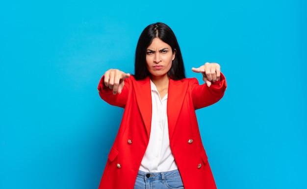 Młoda hiszpańska kobieta wskazująca przed kamerą palcami i gniewną miną, mówiącą ci, abyś wykonał swój obowiązek