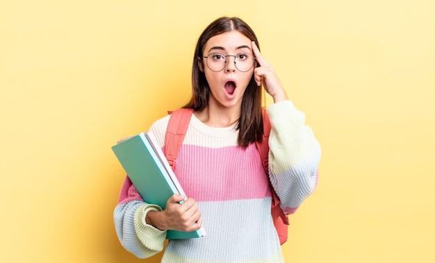 Młoda hiszpańska kobieta wygląda na zaskoczoną, realizując nową myśl, pomysł lub koncepcję. koncepcja studenta