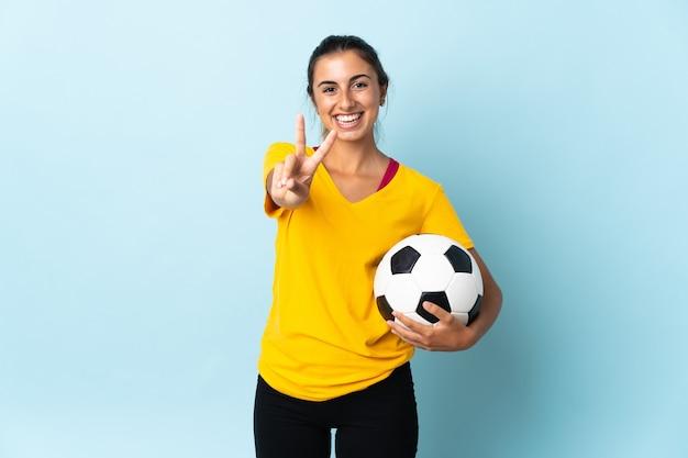 Młoda hiszpańska piłkarz kobieta na białym tle na niebieskiej ścianie uśmiecha się i pokazuje znak zwycięstwa