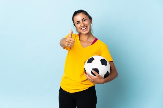 Młoda hiszpańska piłkarz kobieta na białym tle na niebiesko z kciukami do góry, ponieważ stało się coś dobrego