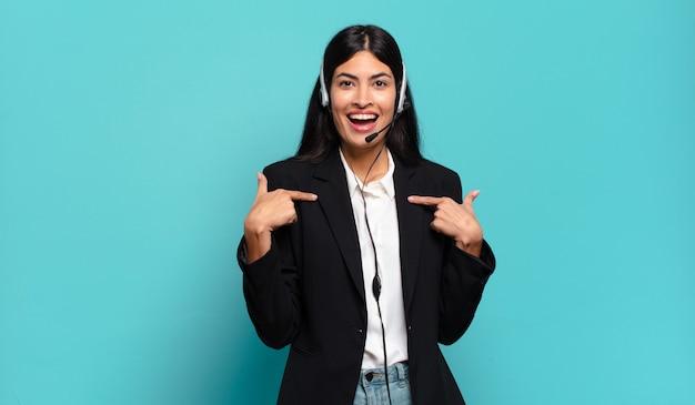 Młoda hiszpańska telemarketerka czuje się szczęśliwa, zaskoczona i dumna, wskazując na siebie z podekscytowanym, zdziwionym spojrzeniem