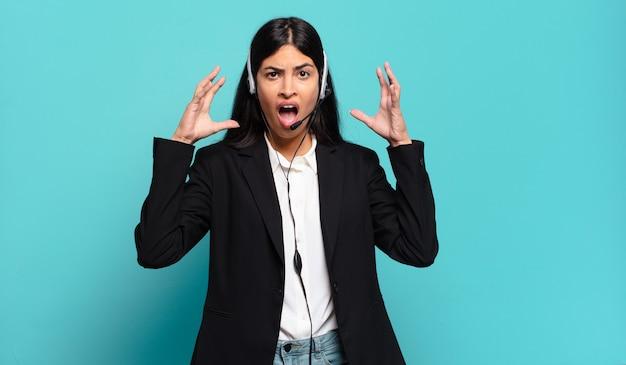 Młoda hiszpańska telemarketerka krzyczy z rękami w górze, czuje się wściekła, sfrustrowana, zestresowana i zdenerwowana