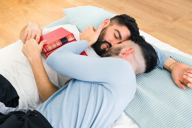 Młoda homoseksualna para kłama na łóżkowym całowaniu