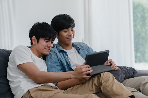 Młoda homoseksualna para używa pastylkę w domu. azjaci lgbtq + mężczyźni chętnie relaksują się przy użyciu technologii, oglądając wspólnie film w internecie, leżąc na kanapie w salonie.