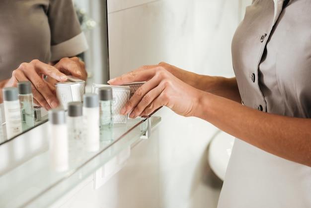 Młoda hotelowa pokojówka stawia akcesoria kąpielowe w łazience