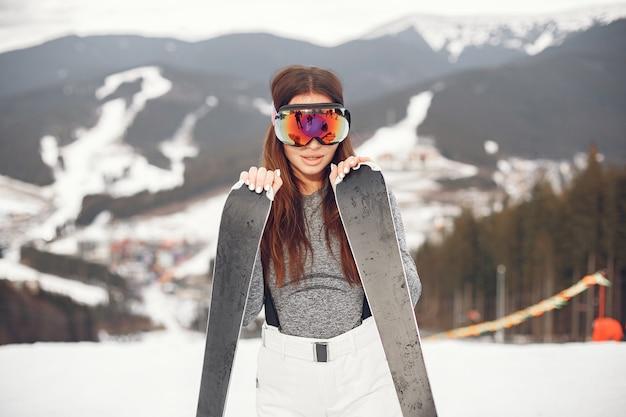 Młoda i aktywna brunetka na nartach. kobieta w zaśnieżonych górach.