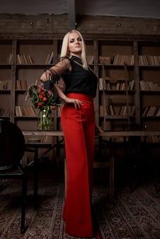 Młoda i atrakcyjna blondynka czyta książkę do biblioteki