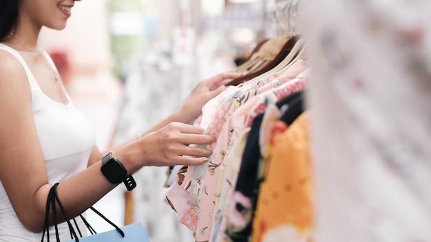 Młoda i atrakcyjna kobieta robi zakupy i wybiera ubrania.
