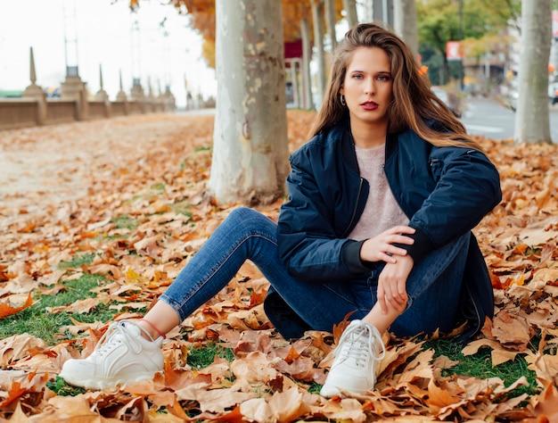 Młoda i atrakcyjna kobieta z długimi włosami pozuje do kamery w parku jesienią.
