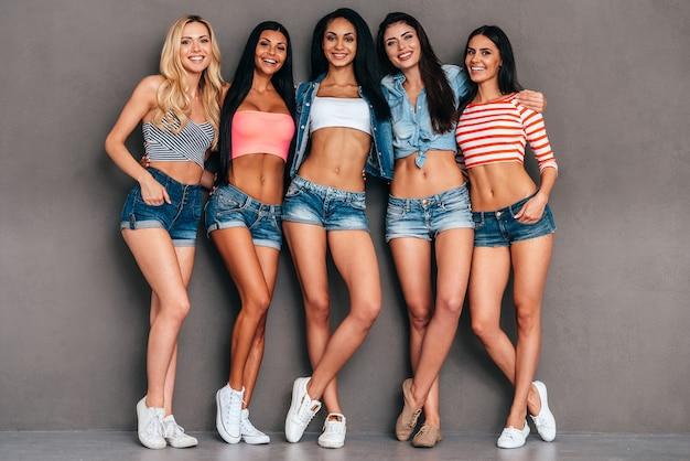 Młoda i beztroska. pełna długość pięciu pięknych młodych kobiet, które łączą się i uśmiechają, stojąc na szarym tle