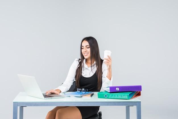 Młoda i biznesowa kobieta pracuje w biurze na białym tle