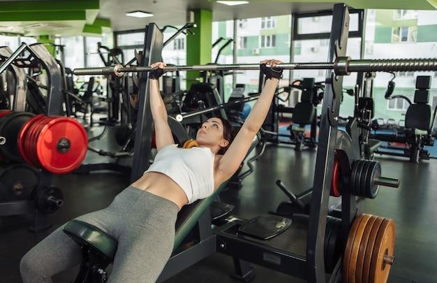 Młoda i kobieta w strojach sportowych praktykujących wyciskanie na ławce skośnej w siłowni