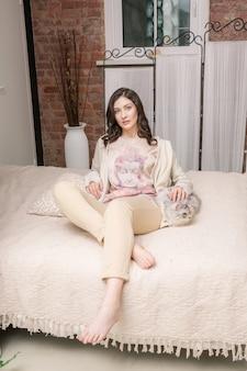 Młoda i ładna kobieta, leżąc na łóżku z kotem.