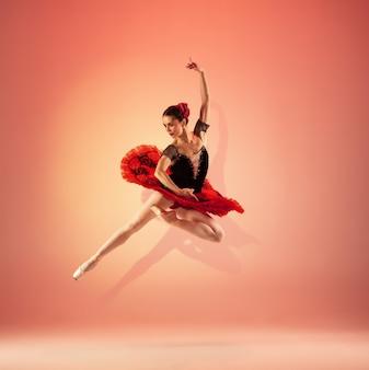 Młoda i niesamowicie piękna baletnica pozuje i tańczy w czerwonym studio pełnym światła.