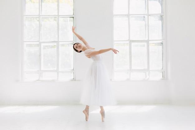 Młoda i niezwykle piękna baletnica pozuje i tańczy w białym studio