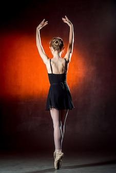 Młoda i niezwykle piękna baletnica pozuje i tańczy w studio. tancerz baletowy mała czarna sukienka.