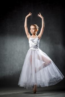 Młoda i niezwykle piękna baletnica pozuje i tańczy w studiu pełnym światła. fotografia w dużej mierze odzwierciedla nieporównywalne piękno klasycznej sztuki baletowej.