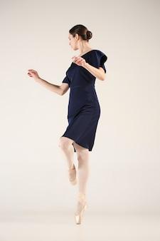 Młoda i niezwykle piękna baletnica tańczy w niebieskim studio