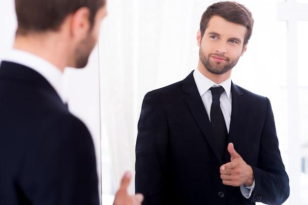 Młoda i odnosząca sukcesy. przystojny młody mężczyzna w pełnym garniturze, wskazujący na siebie i uśmiechający się, stojąc przed lustrem