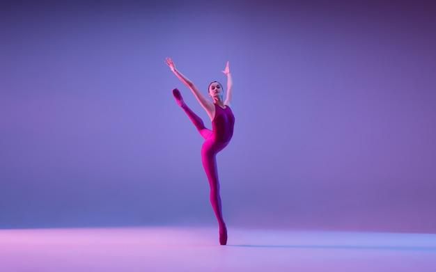 Młoda i pełna wdzięku tancerka baletowa na białym tle na fioletowym tle studio w świetle neonu