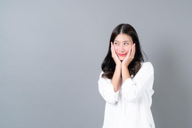 Młoda i piękna azjatka z podekscytowaną twarzą w białej koszuli na szarej ścianie