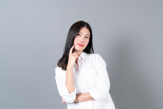 Młoda i piękna azjatka z szczęśliwą twarzą i myśleniem w białej koszuli na szarej ścianie