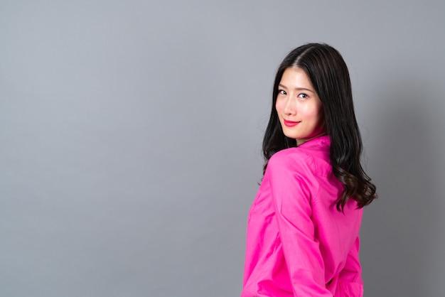 Młoda i piękna azjatka z szczęśliwą uśmiechniętą twarzą w różowej koszuli na szaro