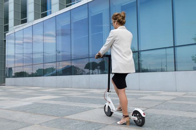 Młoda i piękna bizneswoman jeździ skuterem elektrycznym po mieście