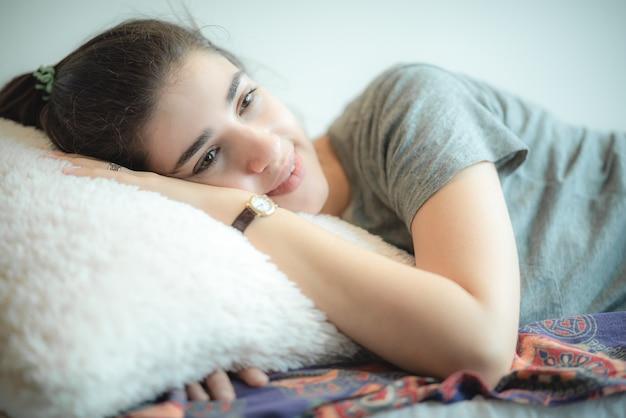 Młoda i piękna dziewczyna drzemała w ciągu dnia, miała słodki sen i relaksowała się, a następnie uśmiechała się na jej twarzy, koncepcja stylu życia w domu, spanie na kanapie, chłodny i przytulny dom.
