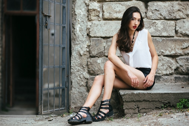 Młoda i piękna dziewczyna siedzi przy drzwiach na kamiennej płycie
