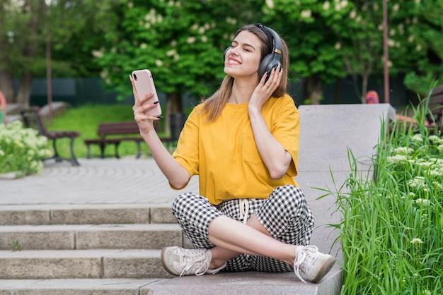 Młoda i piękna kaukaska dziewczyna trzymająca w dłoni smartfon i słuchająca muzyki na słuchawkach