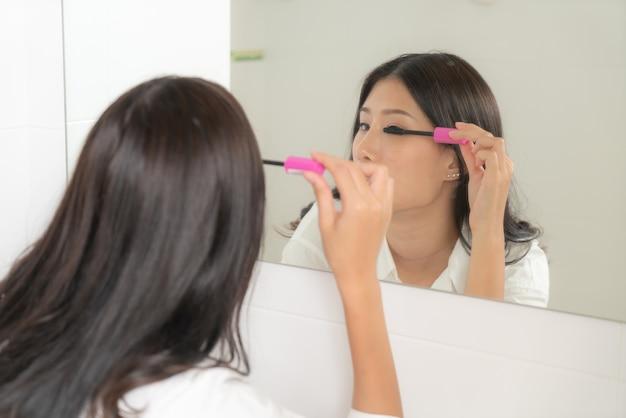 Młoda i piękna kobieta azji makijaż, patrząc w lustro