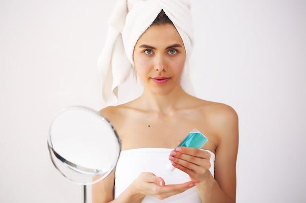 Młoda i piękna kobieta dba o siebie po kąpieli