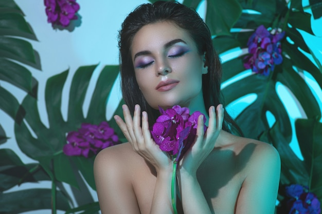 Młoda i piękna kobieta o doskonałej gładkiej skórze trzyma kwiaty orchidei